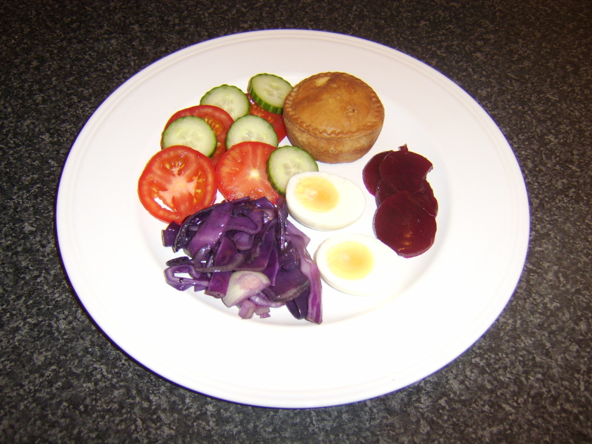 Red cabbage, onion and garlic plated with a pork pie, egg, beetroot and salad.