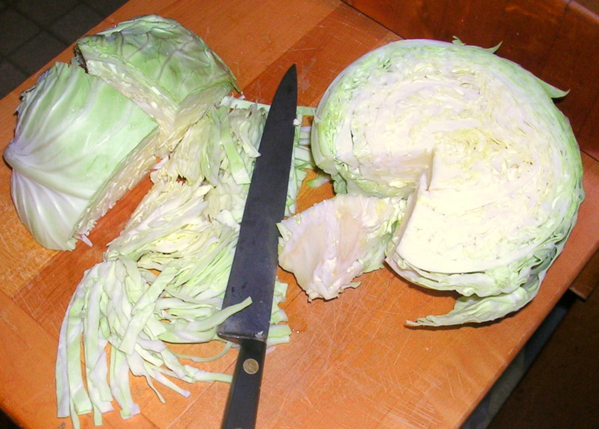 Use a sharp, heavy knife to halve, core, quarter, and finely slice the fresh cabbage.