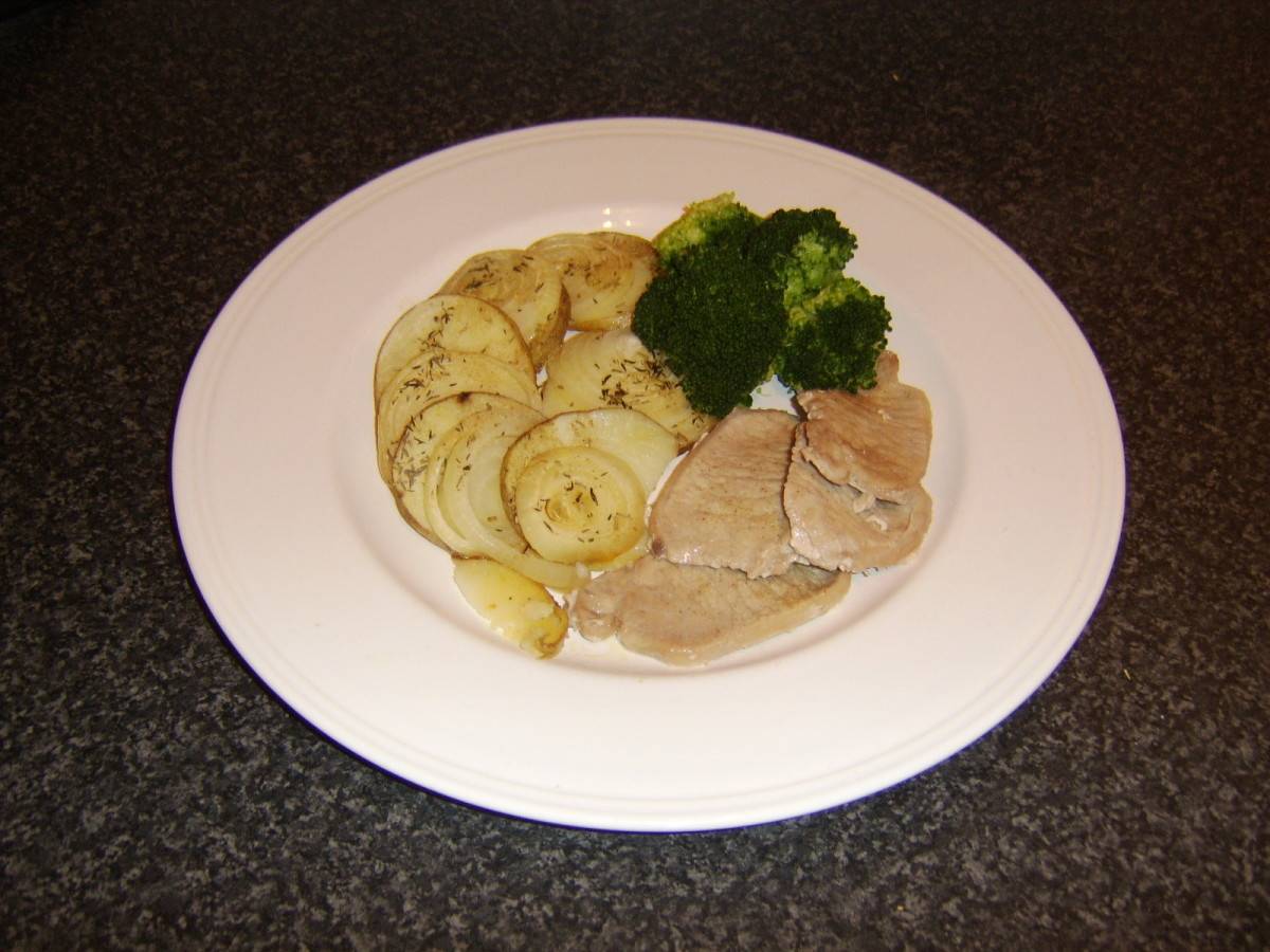 These baked herb potato and onion slices are served with mini leg of pork steaks and broccoli.