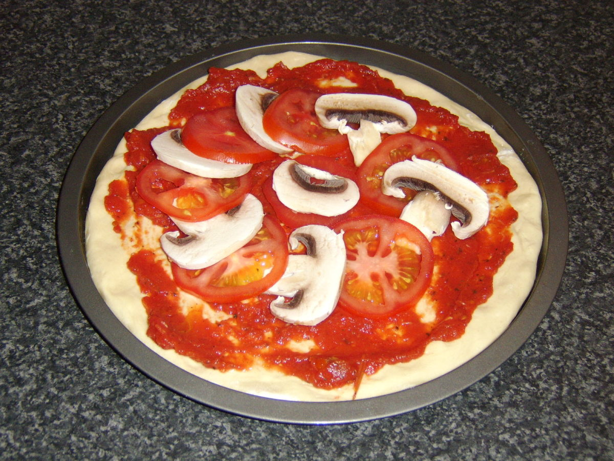 Tomato and mushroom are placed on top of the tomato sauce