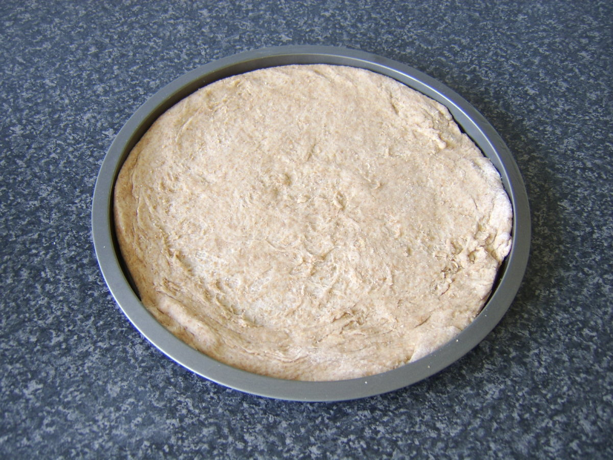 Wholewheat pizza dough stretched out in a baking tin