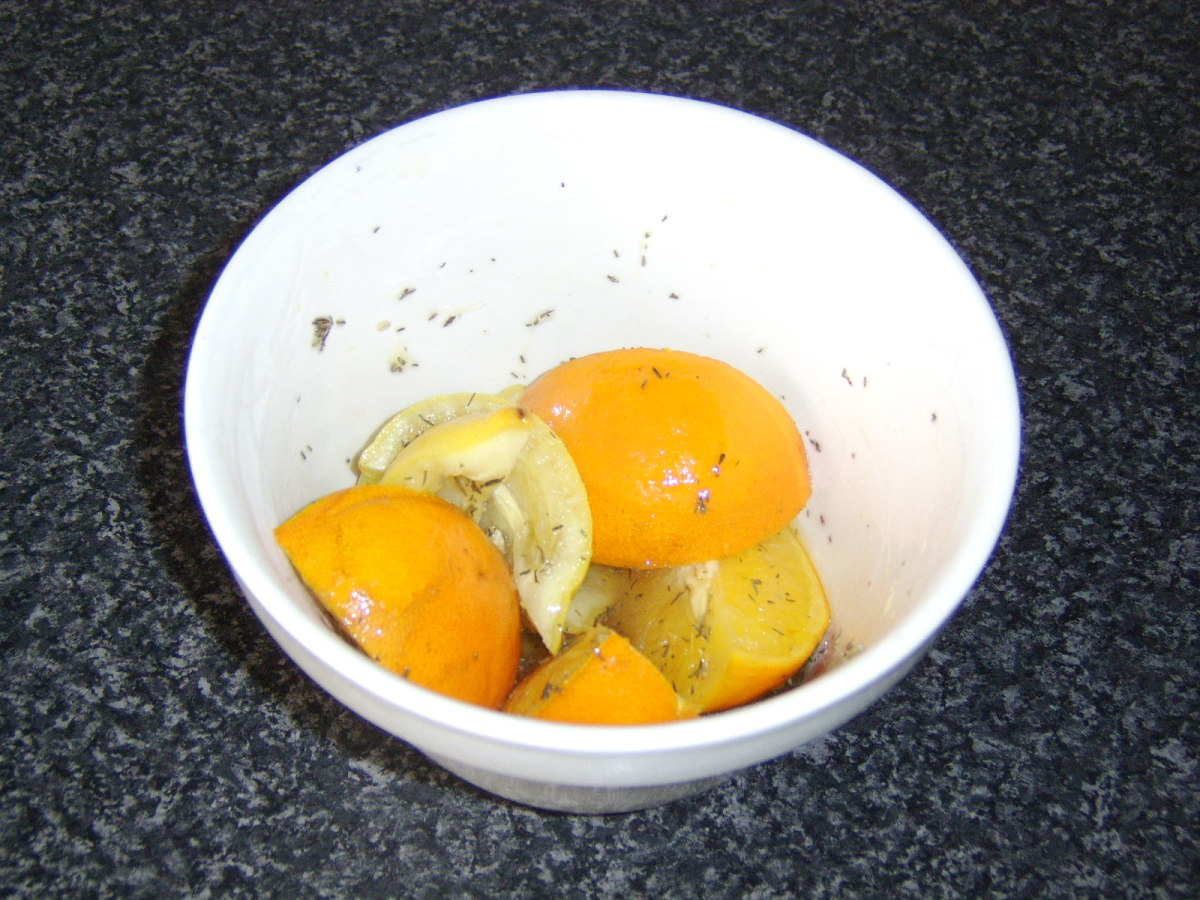 Halved orange and lemon are mixed with honey and thyme