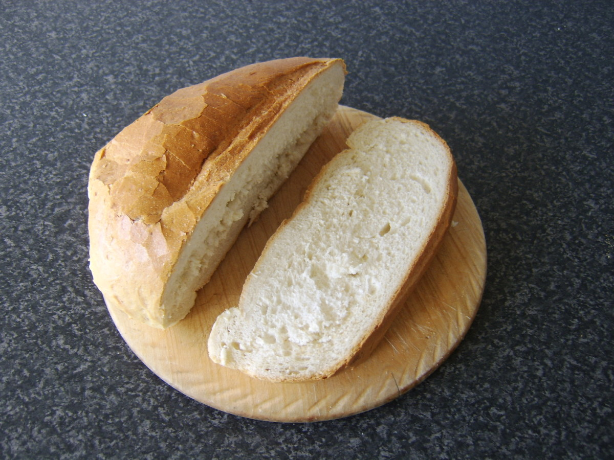 A diagonal slice is cut from a loaf of bread