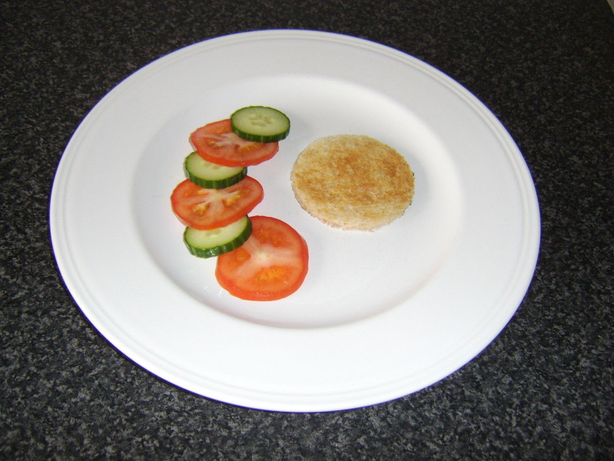 A circle of toast is cut with a large drinking glass and plated with the salad