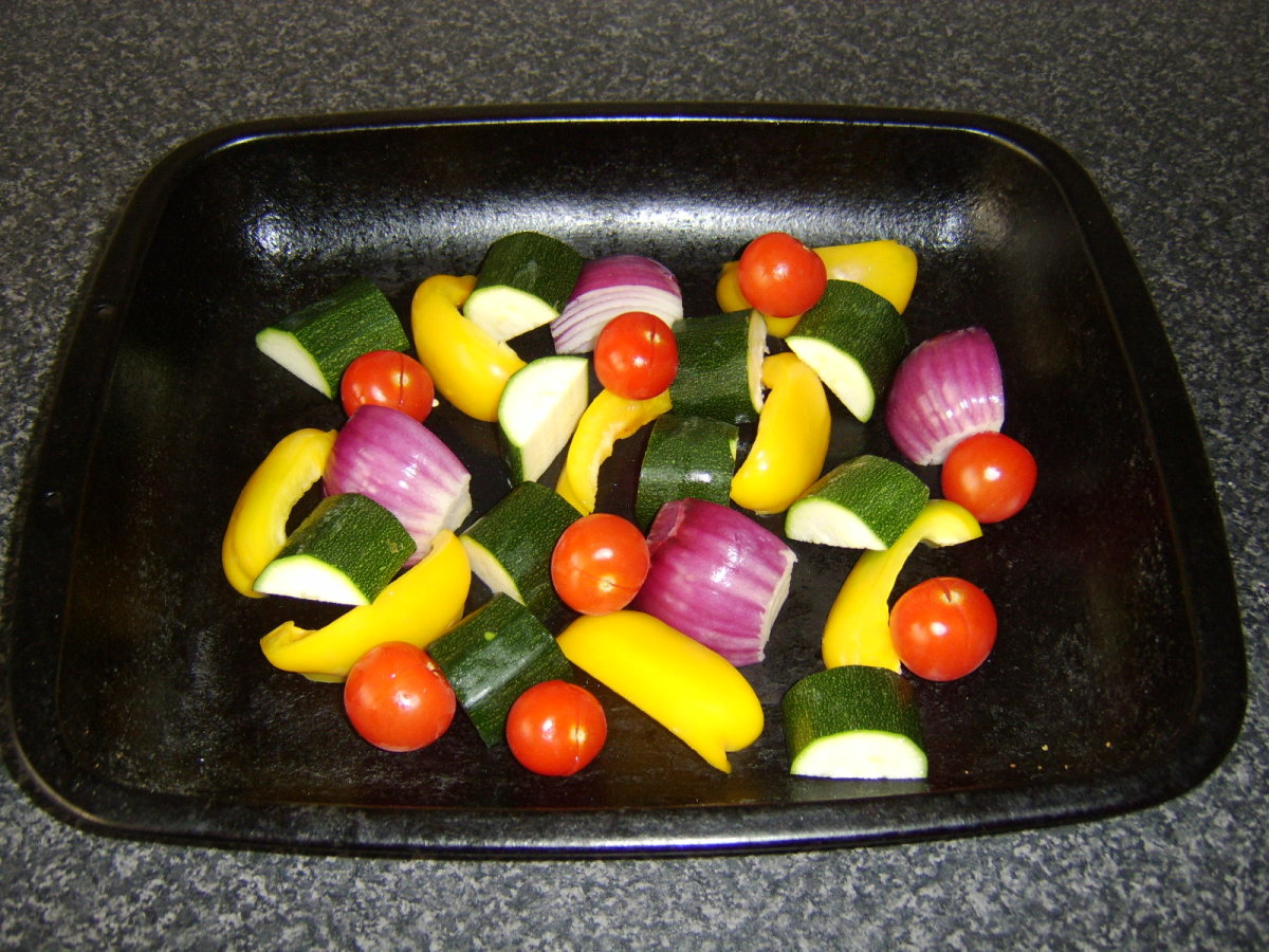 Mediterranean vegetables are roughly chopped and scattered in a baking tray
