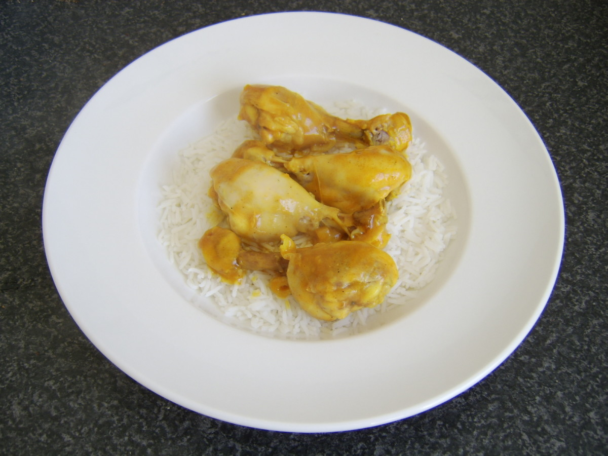 The chicken drumsticks are removed from the casserole and laid on the bed of rice before the curry sauce is spooned over the top