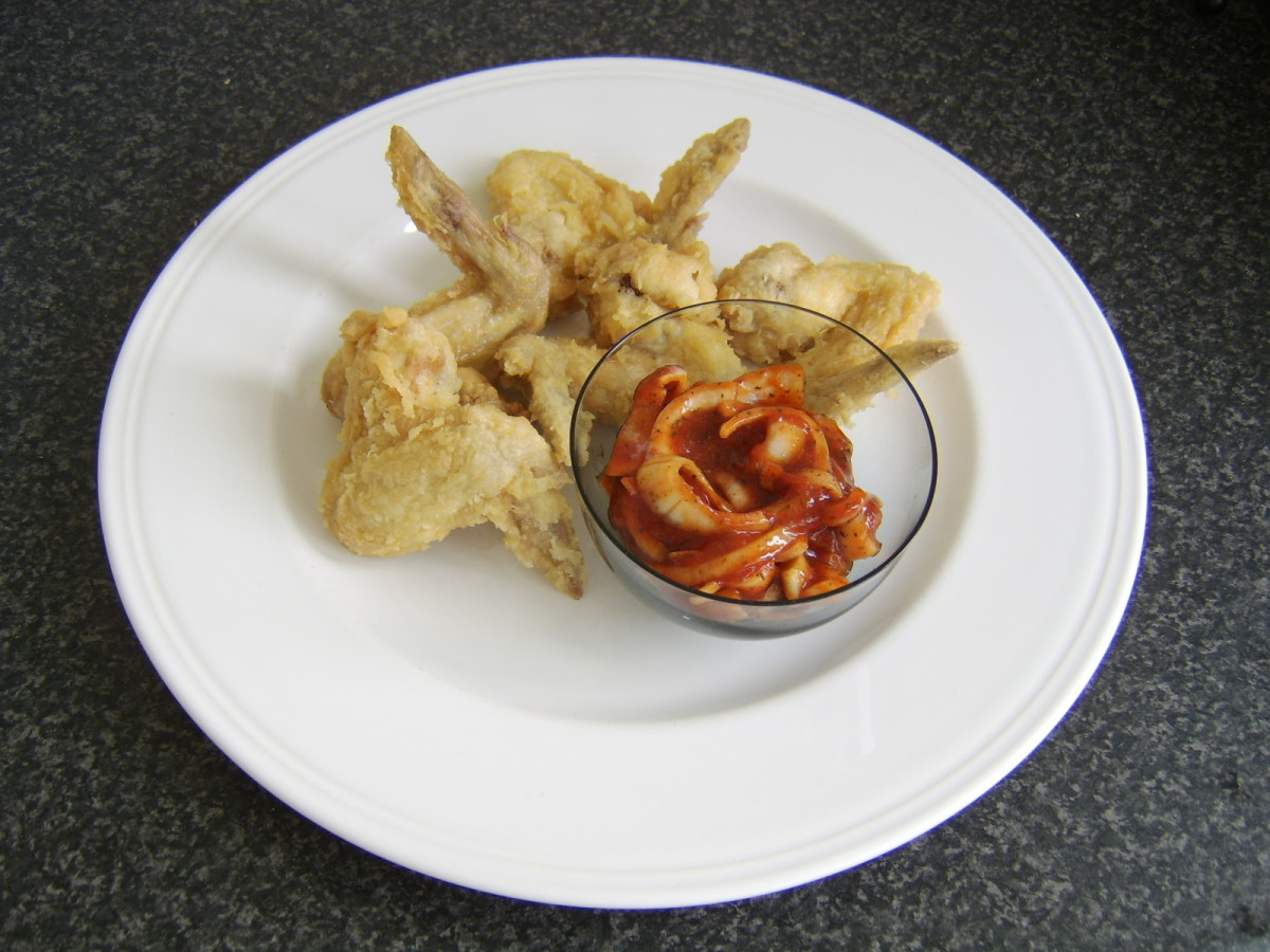 The spiced onions are added to a small dish and plated with the deep fried chicken wings clustered around it