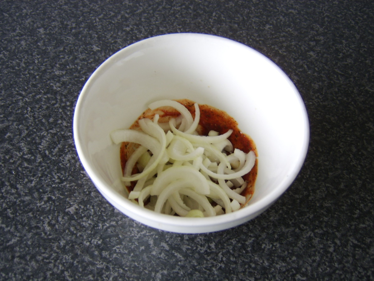 The sliced onions are added to the prepared spice mix