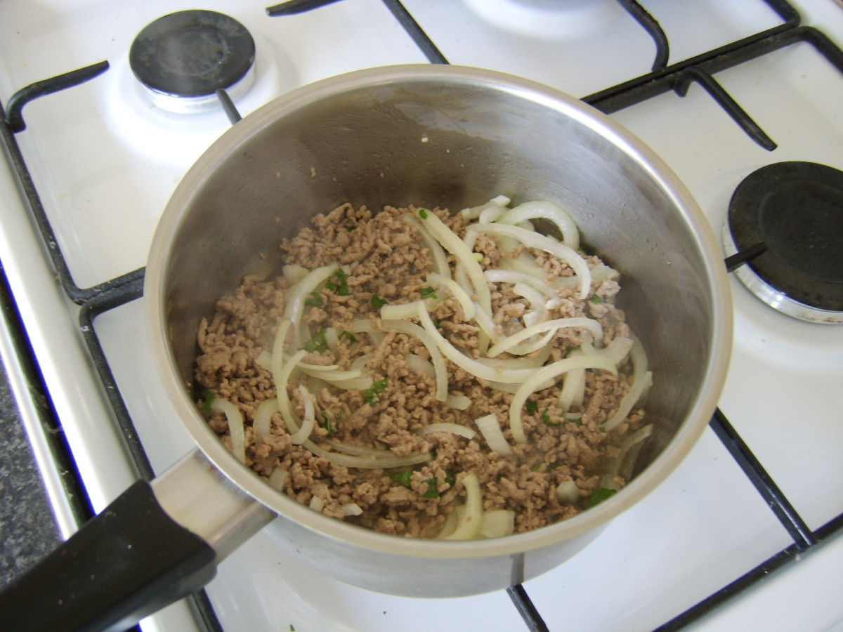 The lamb is browned in a dry saucepan before the thinly sliced onion and chopped mint are added.