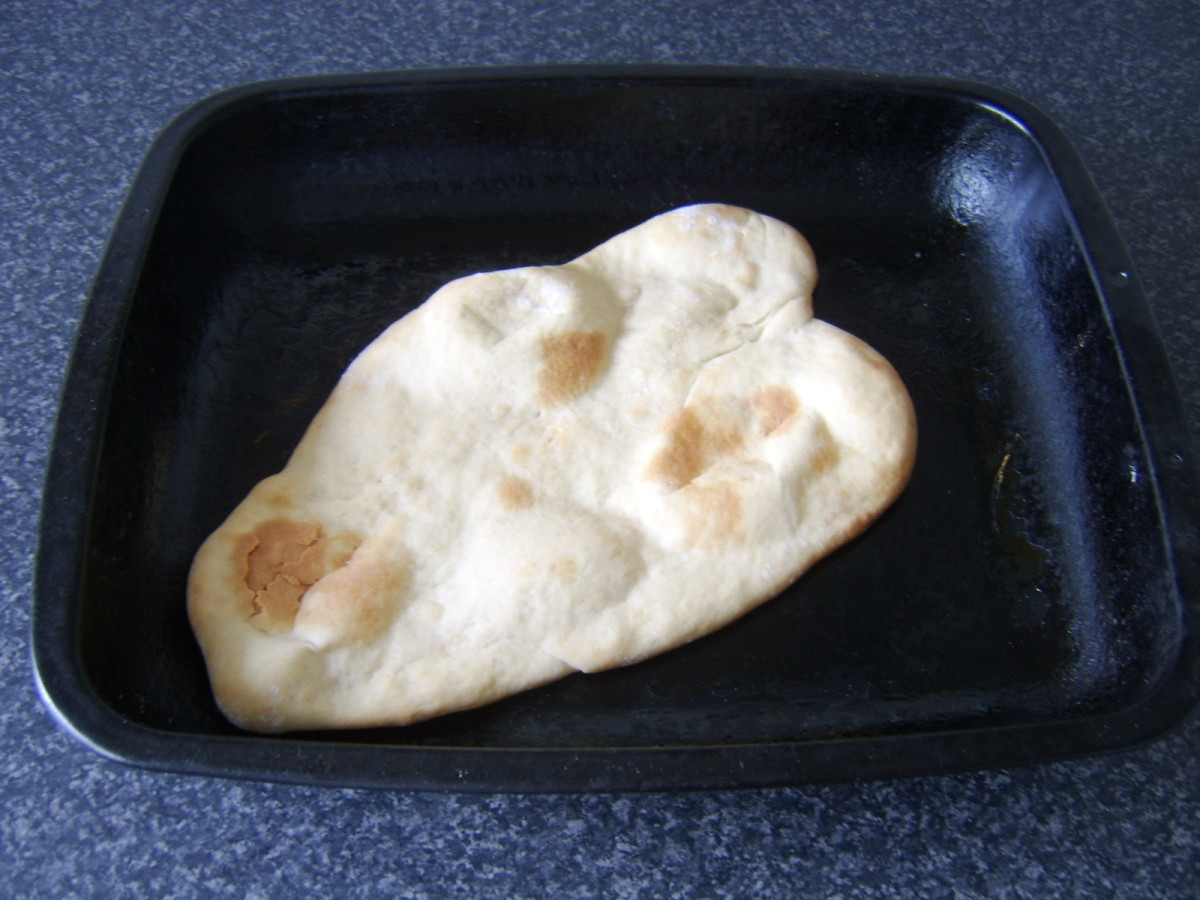 Naan bread removed from the oven, ready to be glazed with melted butter and served