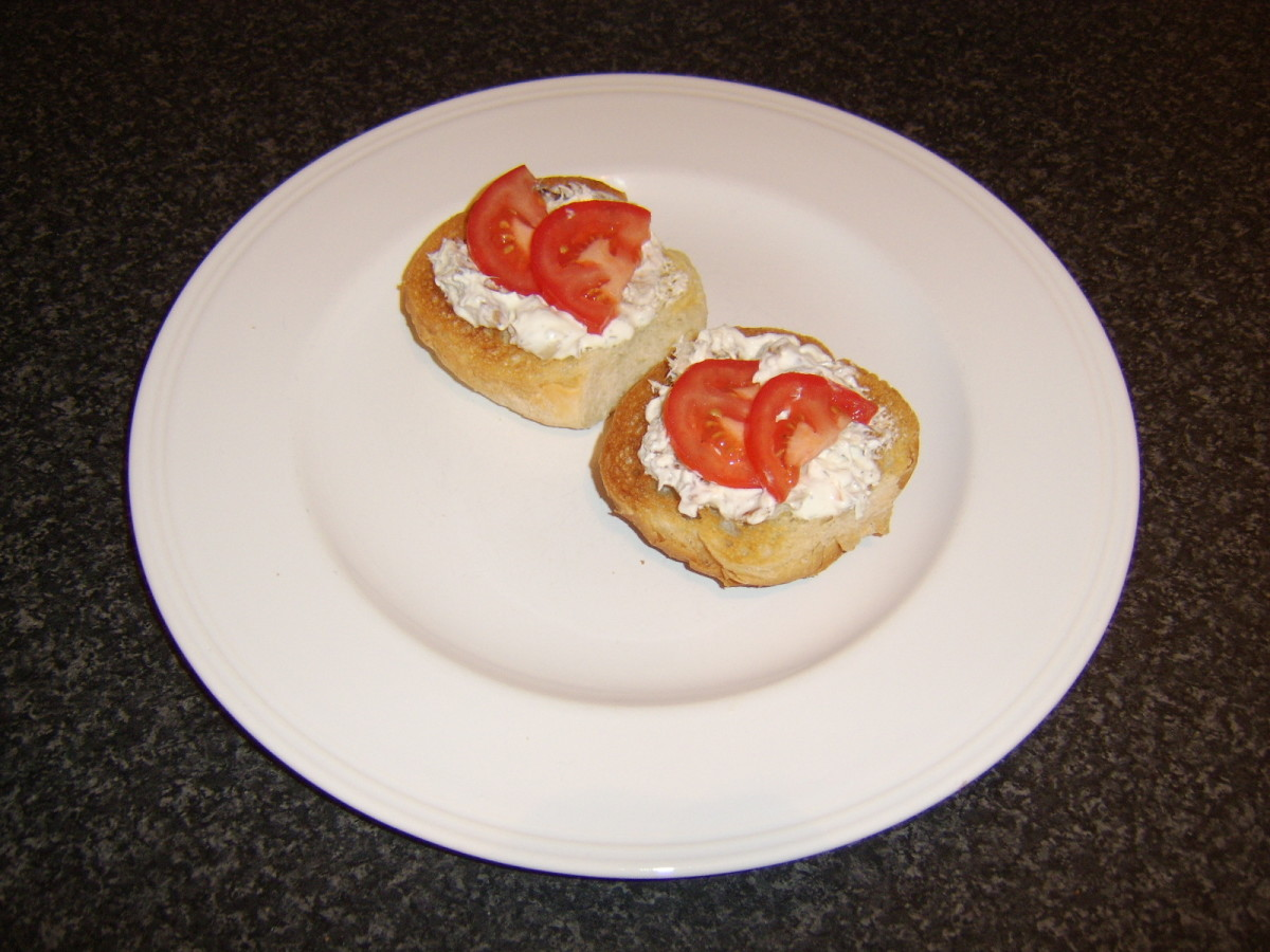 The smoked mackerel and soured cream is spread on the hot rolls and garnished firstly with a little bit of tomato