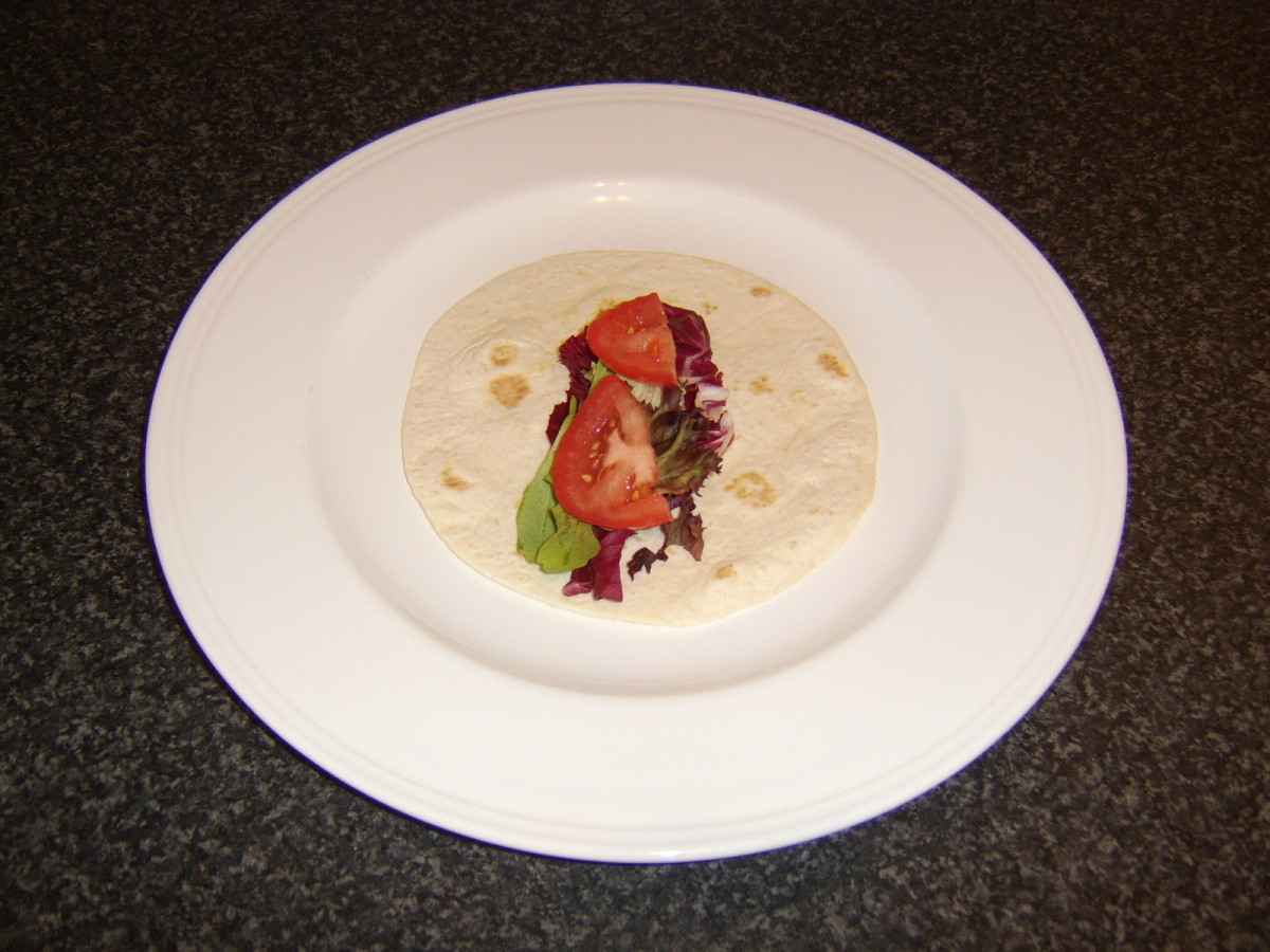 Salad leaves and tomato slices are added to the tortilla wrap
