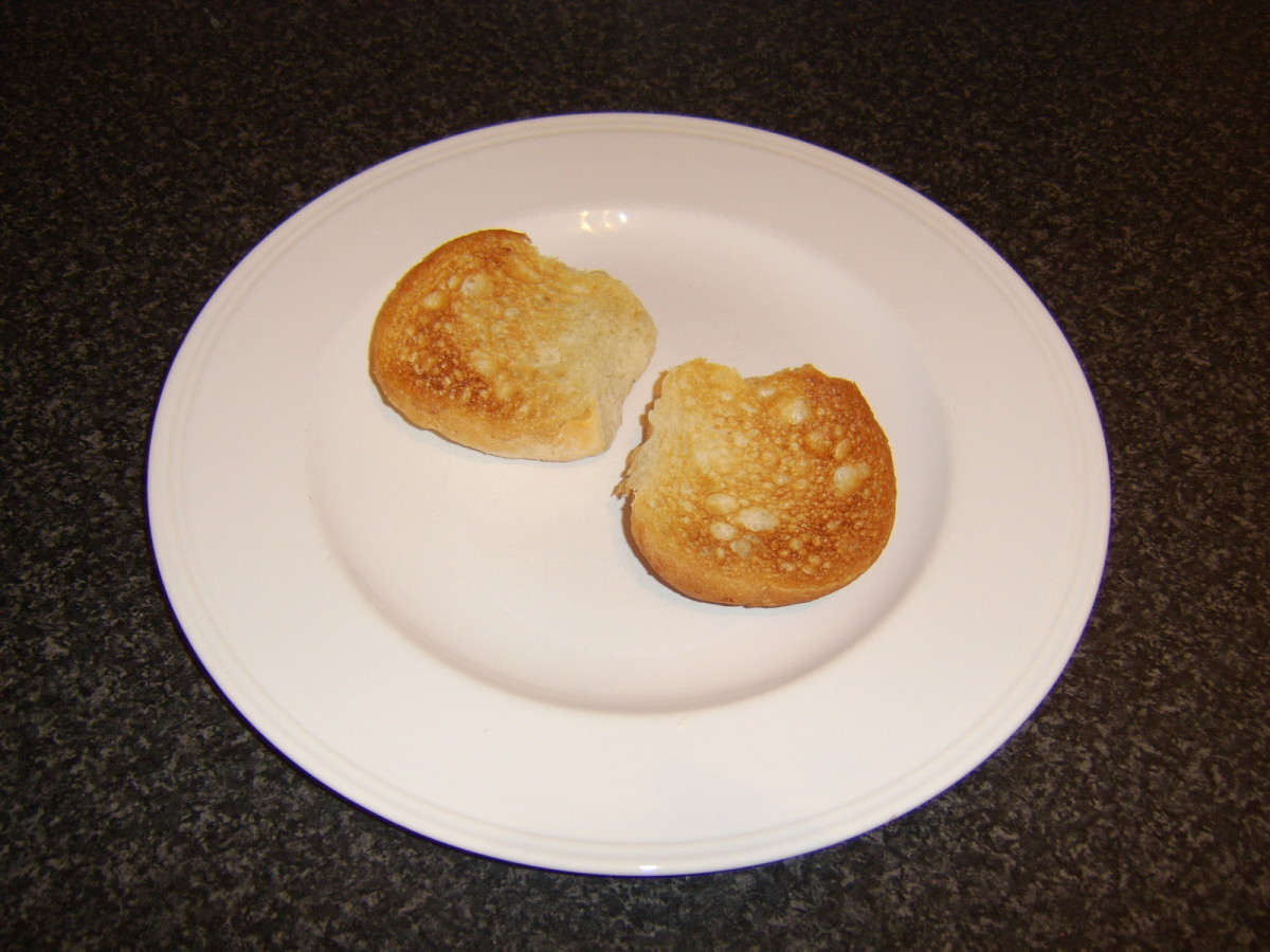 The bread roll is halved horizontally and lightly toasted on each side