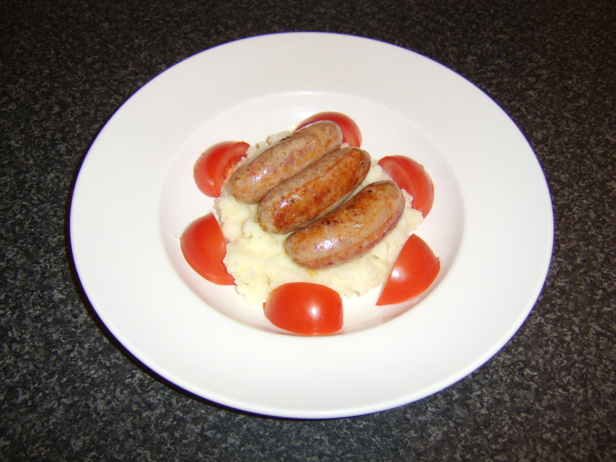 The sausages are laid on the mash with the tomato wedges arranged around the edge