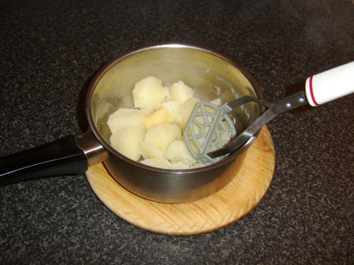 Butter is added to the potatoes and they are mashed in the traditional fashion