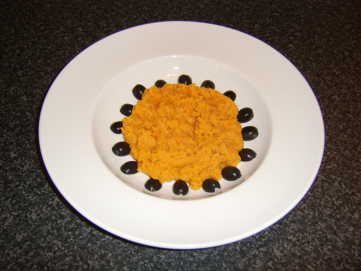 The sweet potato is piled in the centre of the plate and surrounded by the pitted and halved black olives