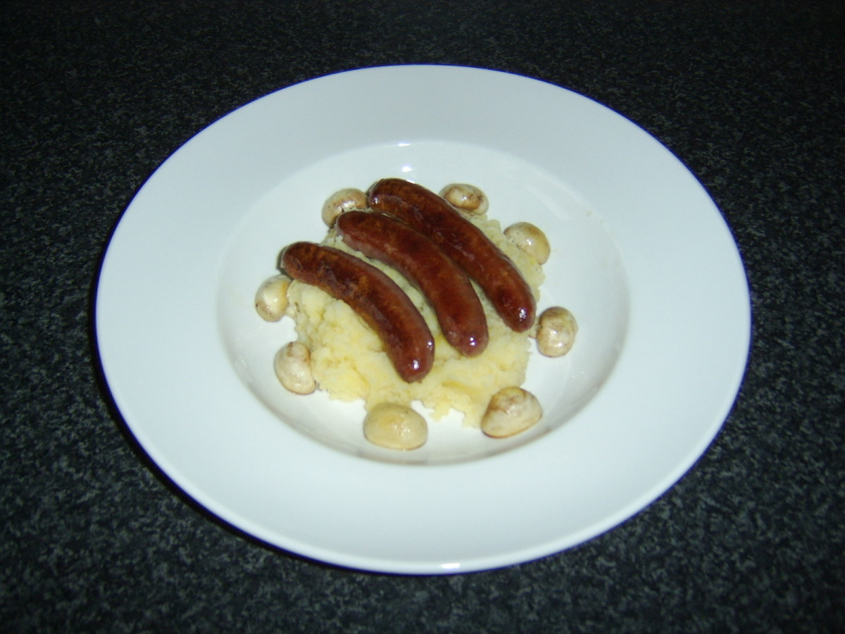 The bangers are laid on top of the mash and the mushroom halves around the edge of the plate