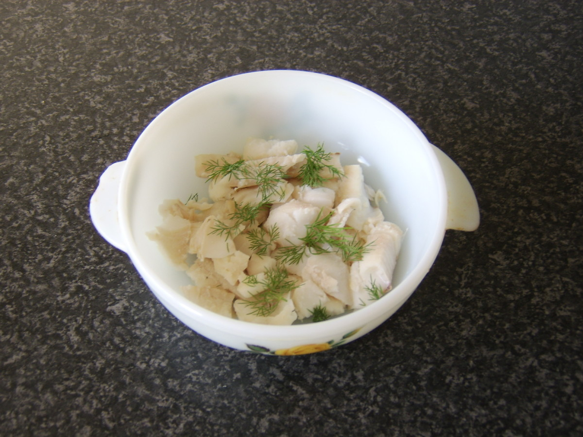 The cooked and cooled whiting fillet is broken in to pieces and laid in the bottom of a casserole dish with fresh dill