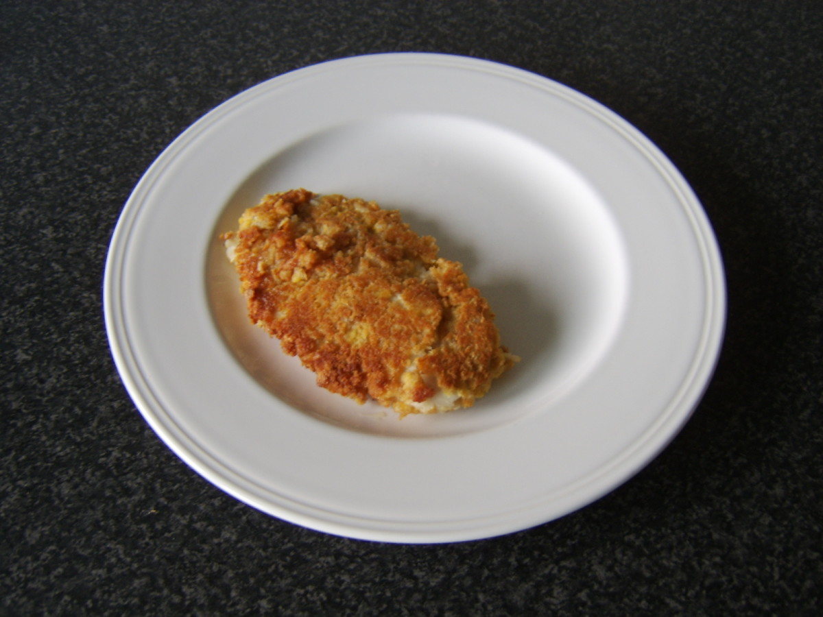 The pan fried whiting fillet is added to a plate