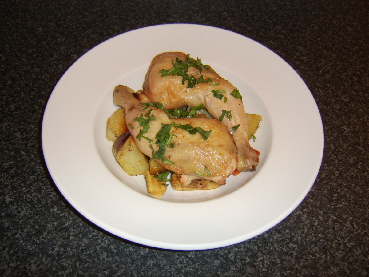 The roasted chicken leg portions are laid on top of the vegetables on a serving plate