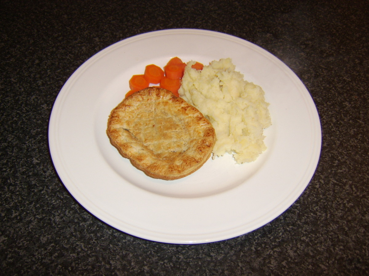 The potato and parsnip mash is spooned on to the plate beside the meat pie and some boiled carrots
