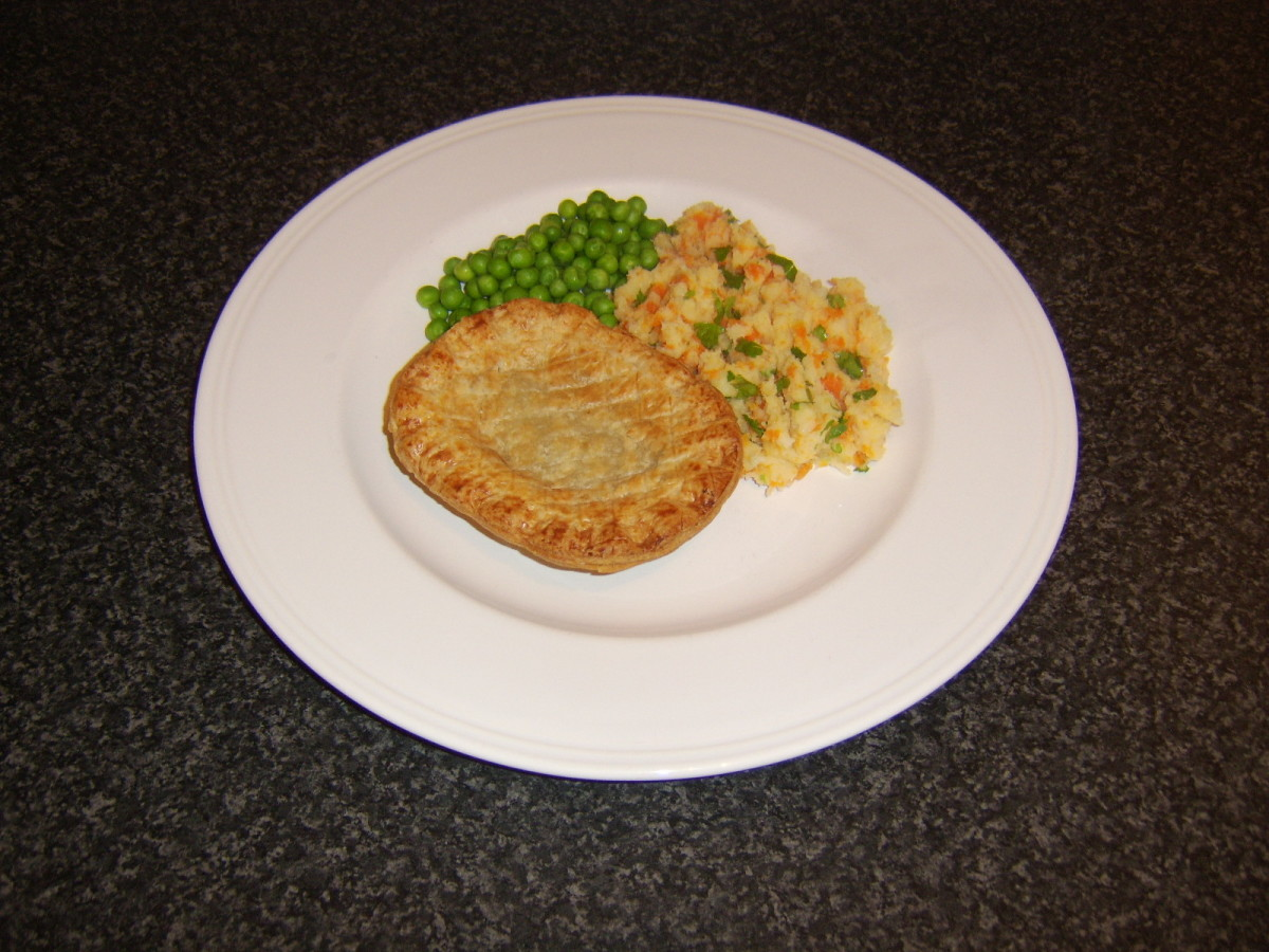 The mash is plated alongside the pie and the peas are added to the plate
