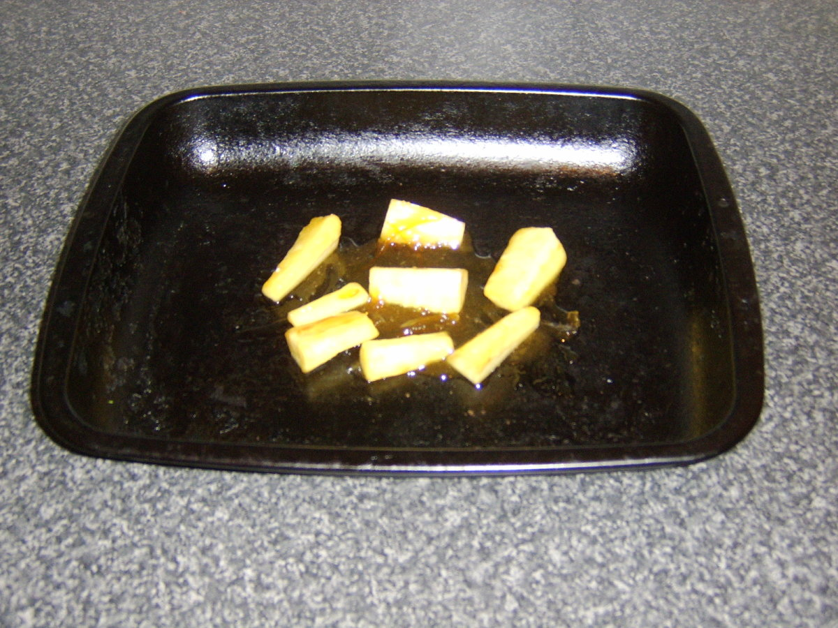 The parsnips are laid on a roasting tray
