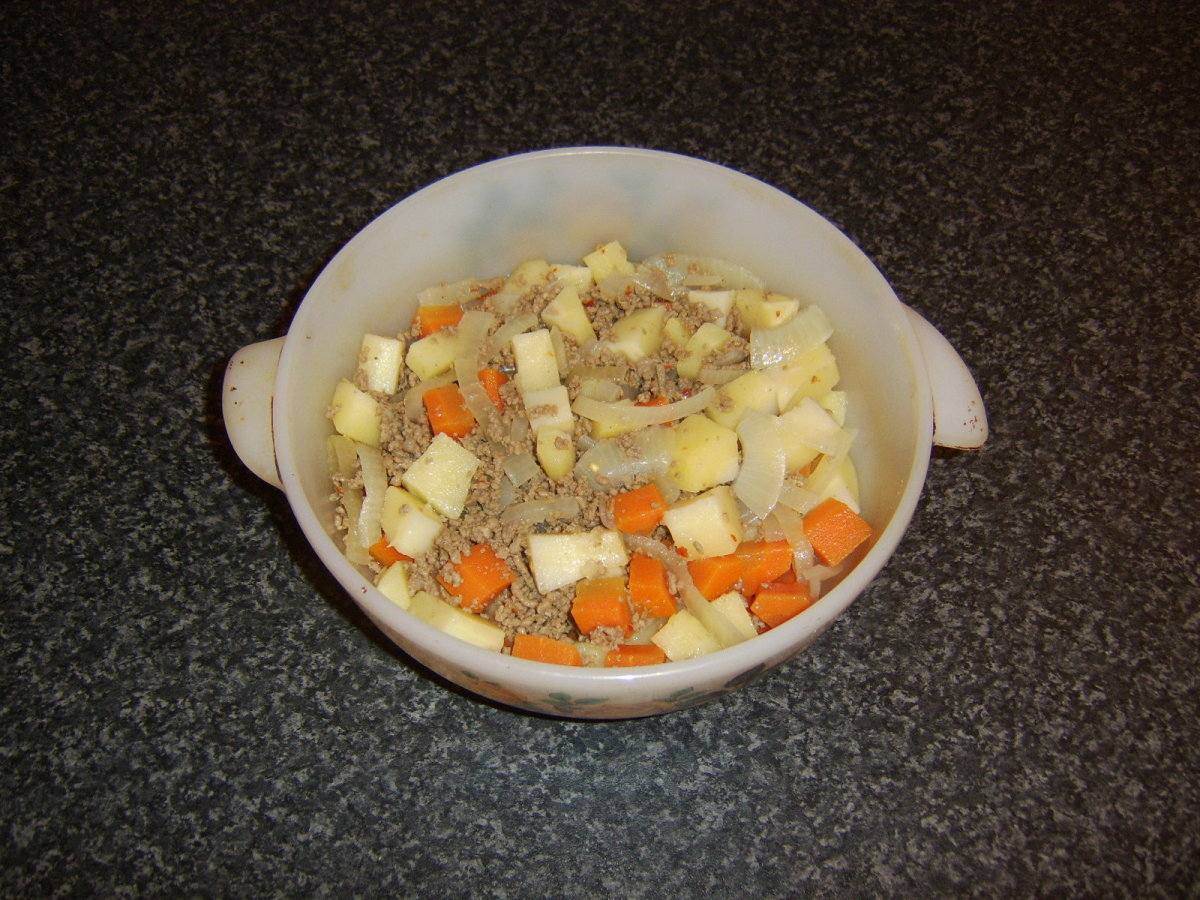 The beef and vegetables are firstly spread on the bottom of the casserole dish