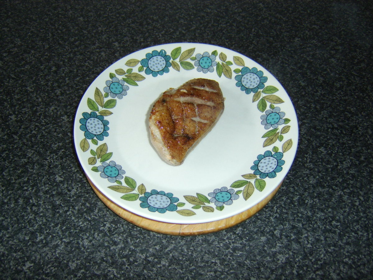 Duck breast is rested on a warmed plate