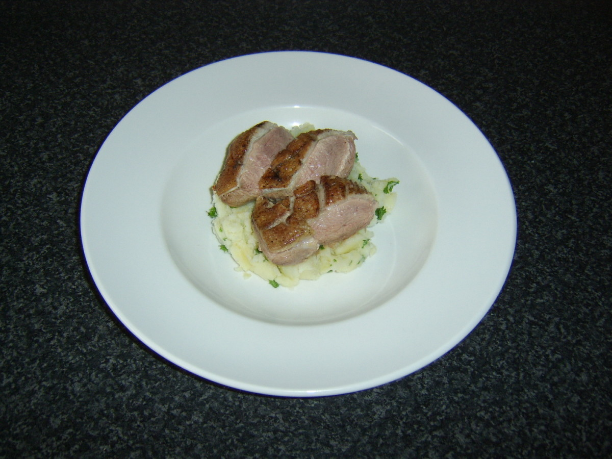 Sliced duck breast is laid on top of the mash