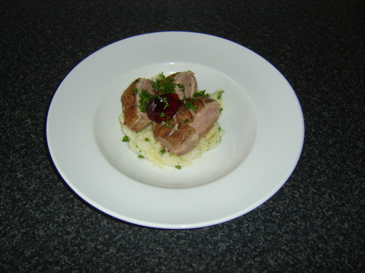 The pan-fried duck breast is rested before being sliced and served on the bed of mash, garnished with parsley and red currant jelly.