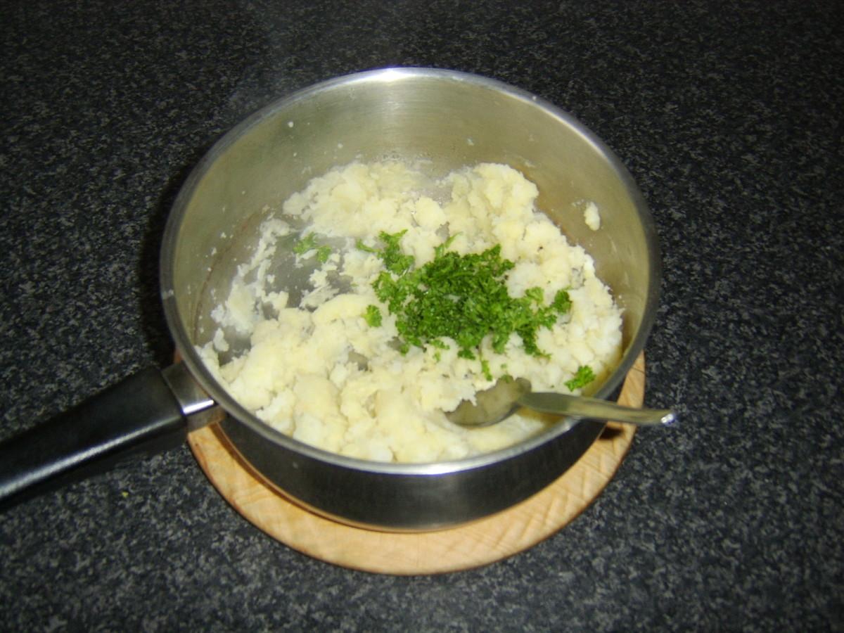 Parsley and garlic is stirred through the mash
