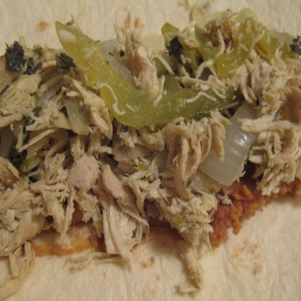 A flour tortilla with refried beans and shredded chicken in salsa.