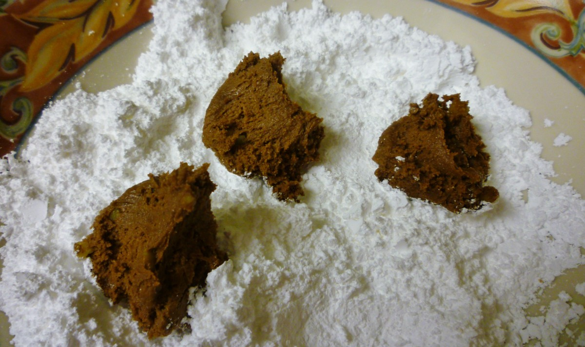 Dropping bits of the cookie batter into powdered sugar and then rolling into a ball shape.