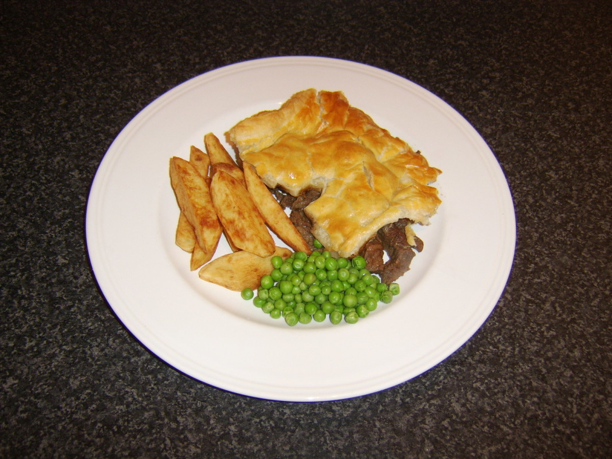 Homemade steak and kidney pie is usually served with accompaniments such as chips and peas