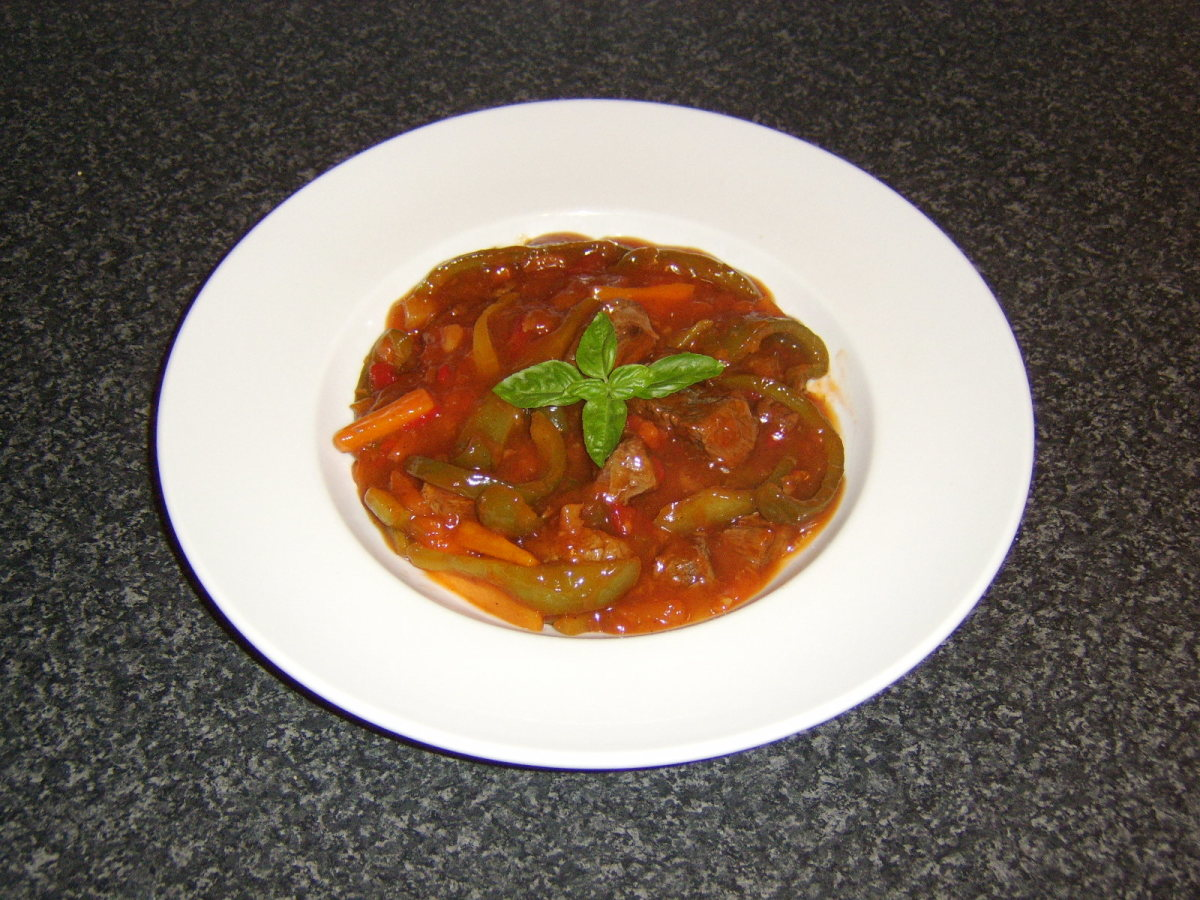 The sweet and sour beef stew is served garnished with a sprig of fresh basil