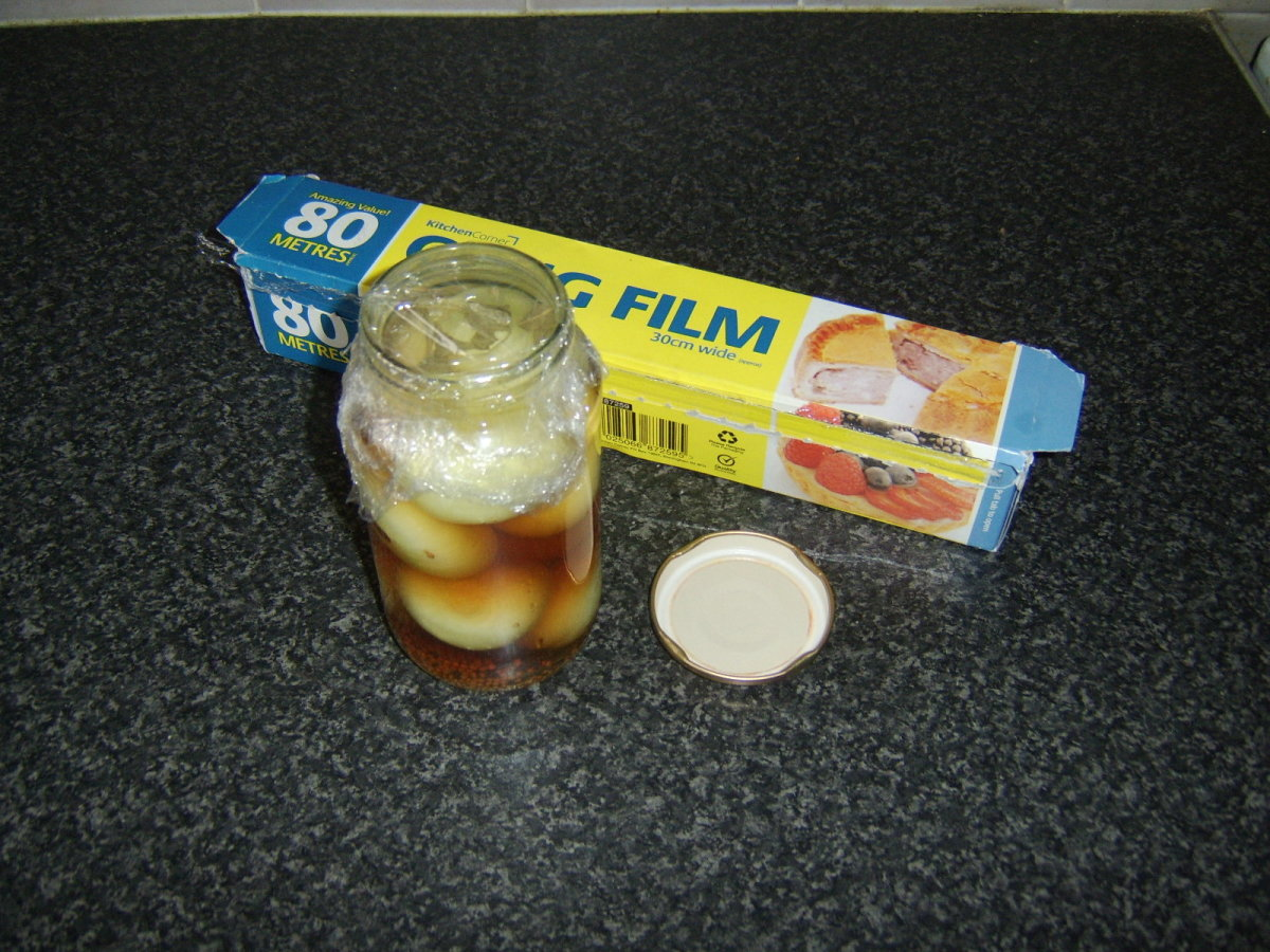 Plastic wrap is placed on the jar before the metal lid