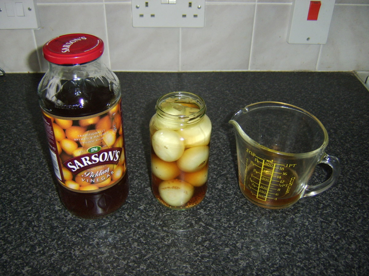 Malt vinegar is poured into the jar with the onions and spices.