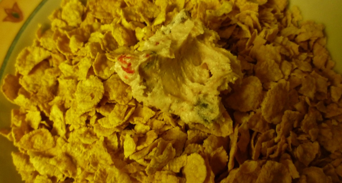 Dropped teaspoonful of cookie dough into cornflakes where they will be rolled into a ball shape.