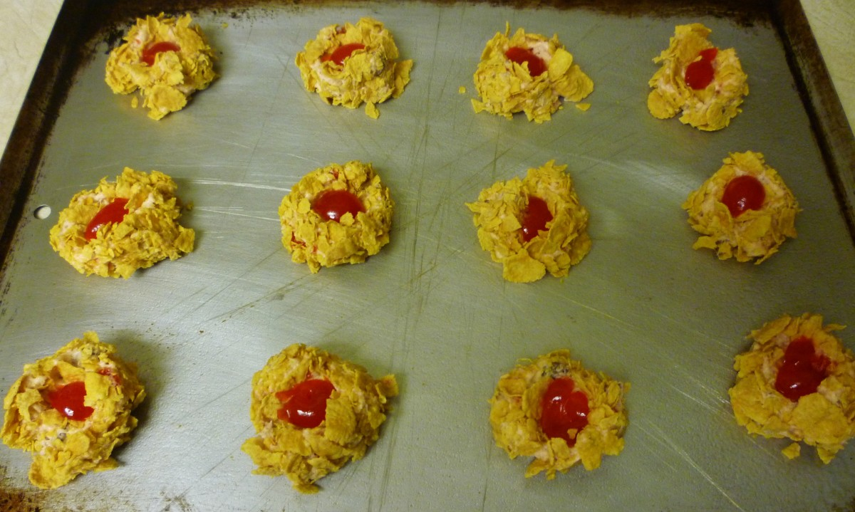 Maraschino cherries adorning the top of the cookies prior to baking.