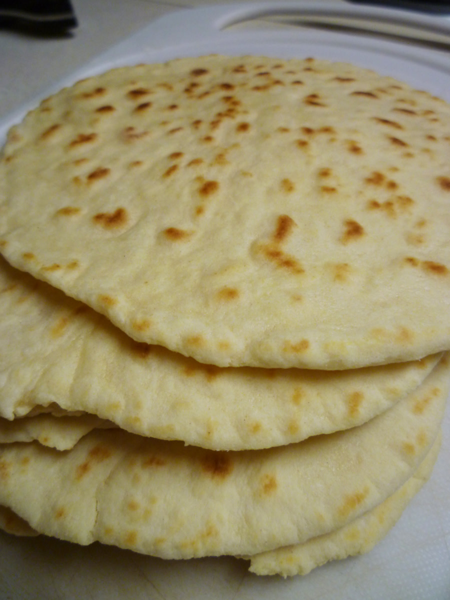 The finished tortillas will have developed golden-brown spots but still remain flexible and soft.