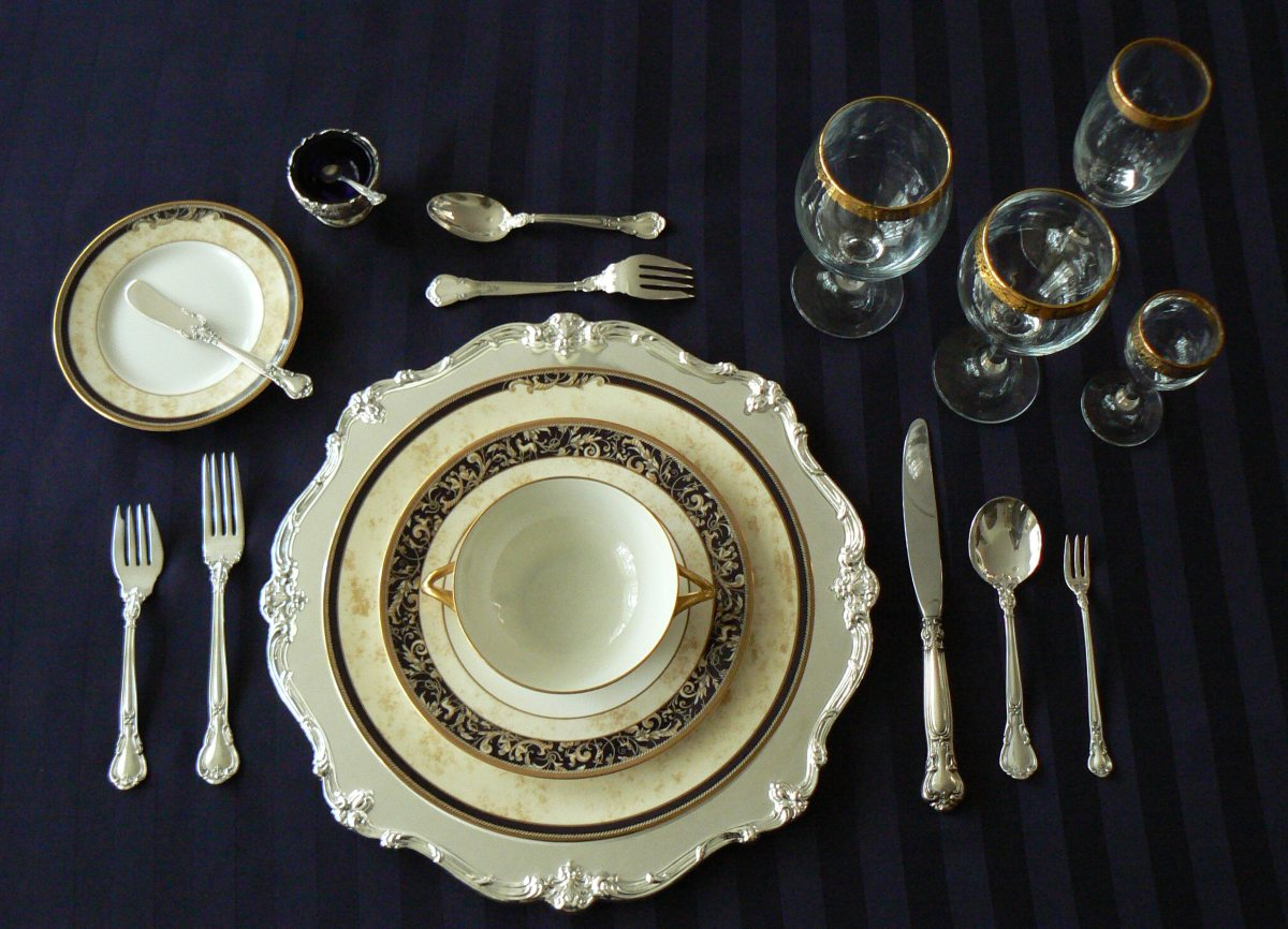 ...to this: A proper place setting complete with soup bowl, salad bowl, salad fork, butter plate and knife, desert spoon, water glass, red and white wine glasses. This setting has added a fork on the right for shellfish. Don't need it? Eliminate it