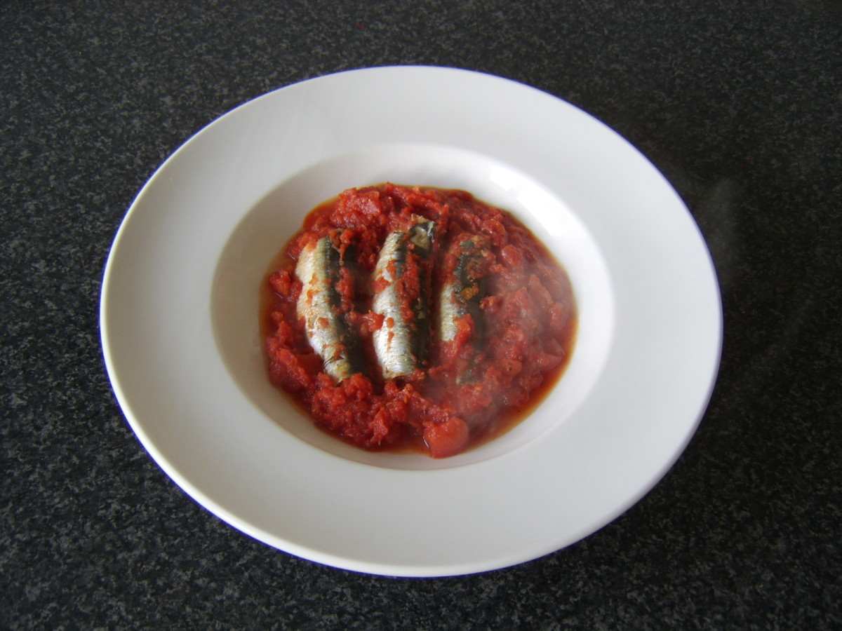 The sardines and tomato sauce are transferred to a serving plate with a large slotted spoon