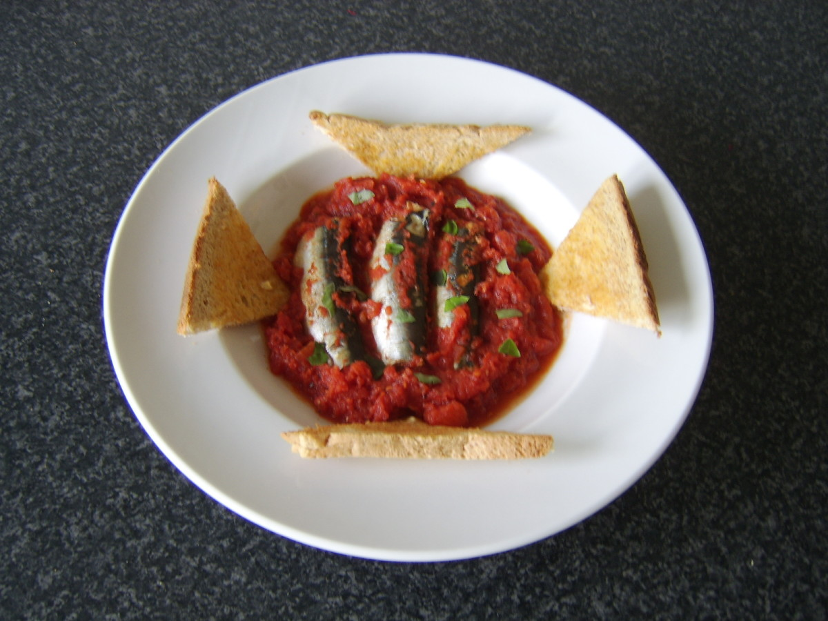 Fresh sardines cooked in homemade tomato sauce are served with hot, buttered toast