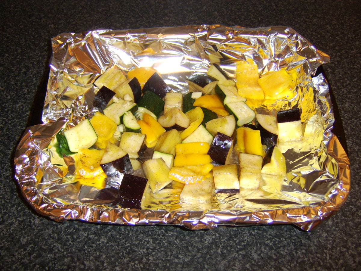 Vegetables are spread in a single layer on a foil lined baking tray