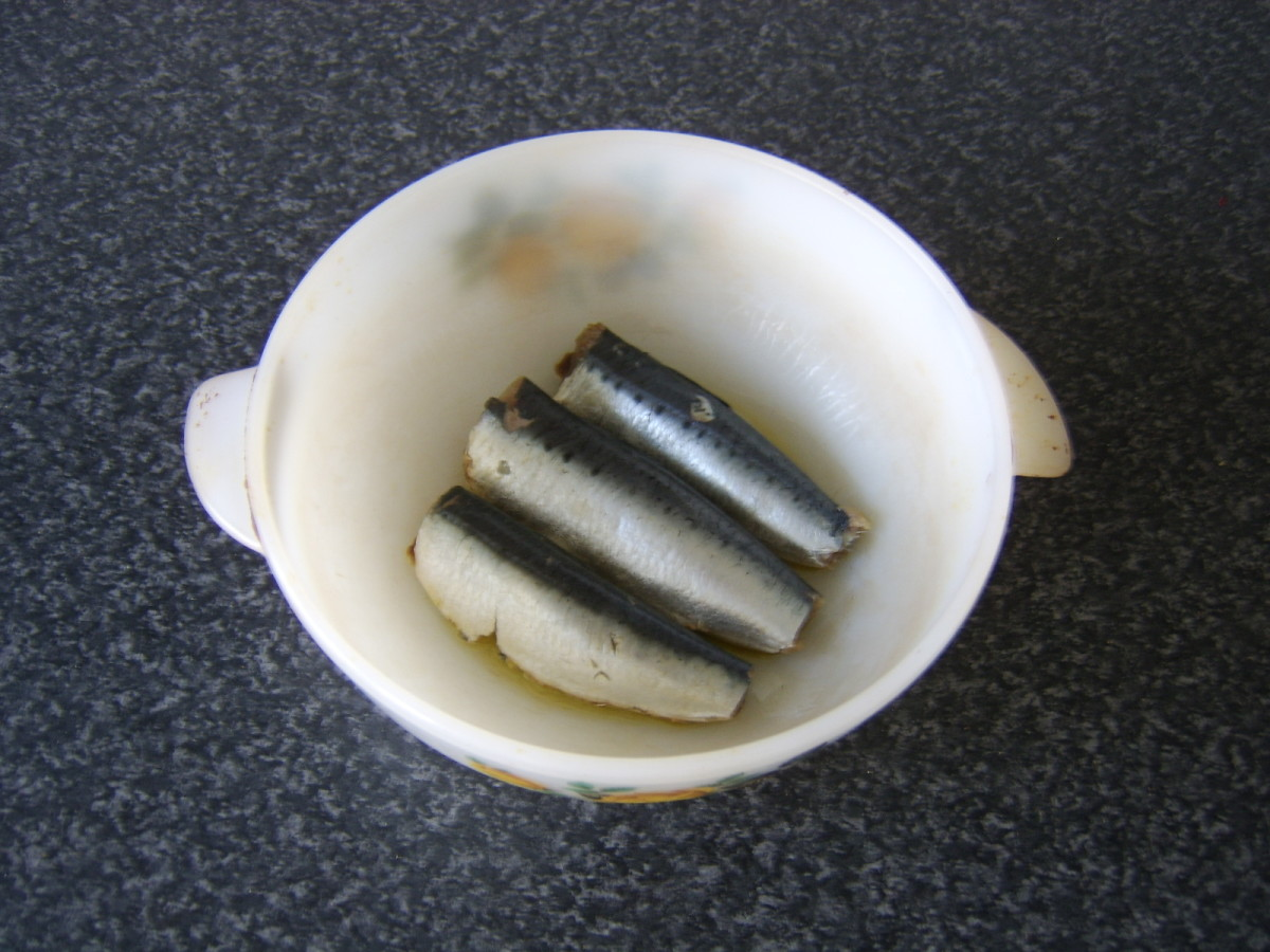 Sardines are laid on drizzled olive oil in a casserole dish