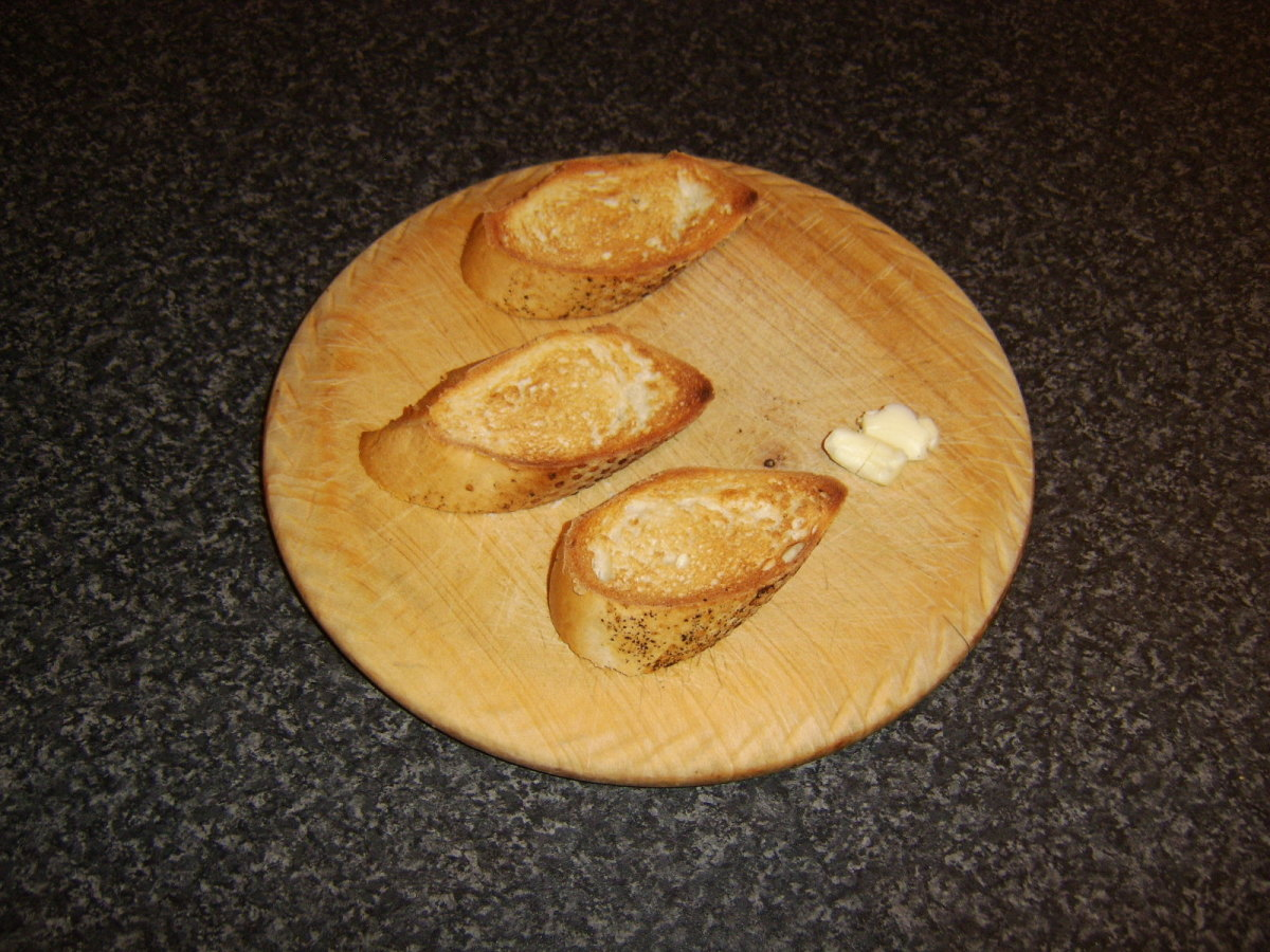 A crushed garlic clove is firstly rubbed over the toasted bread