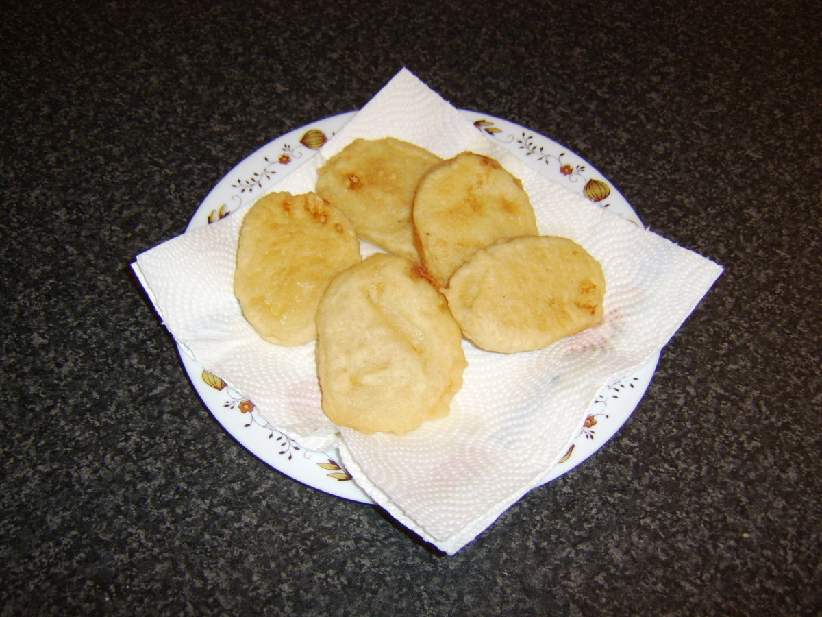Cooked potato fritters are drained on kitchen paper.