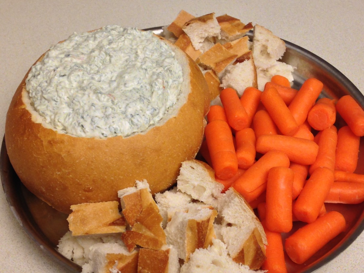 Spinach Dip made with Knorr dry vegetable soup mix. Served in a sourdough bread bowl with bread and carrots.