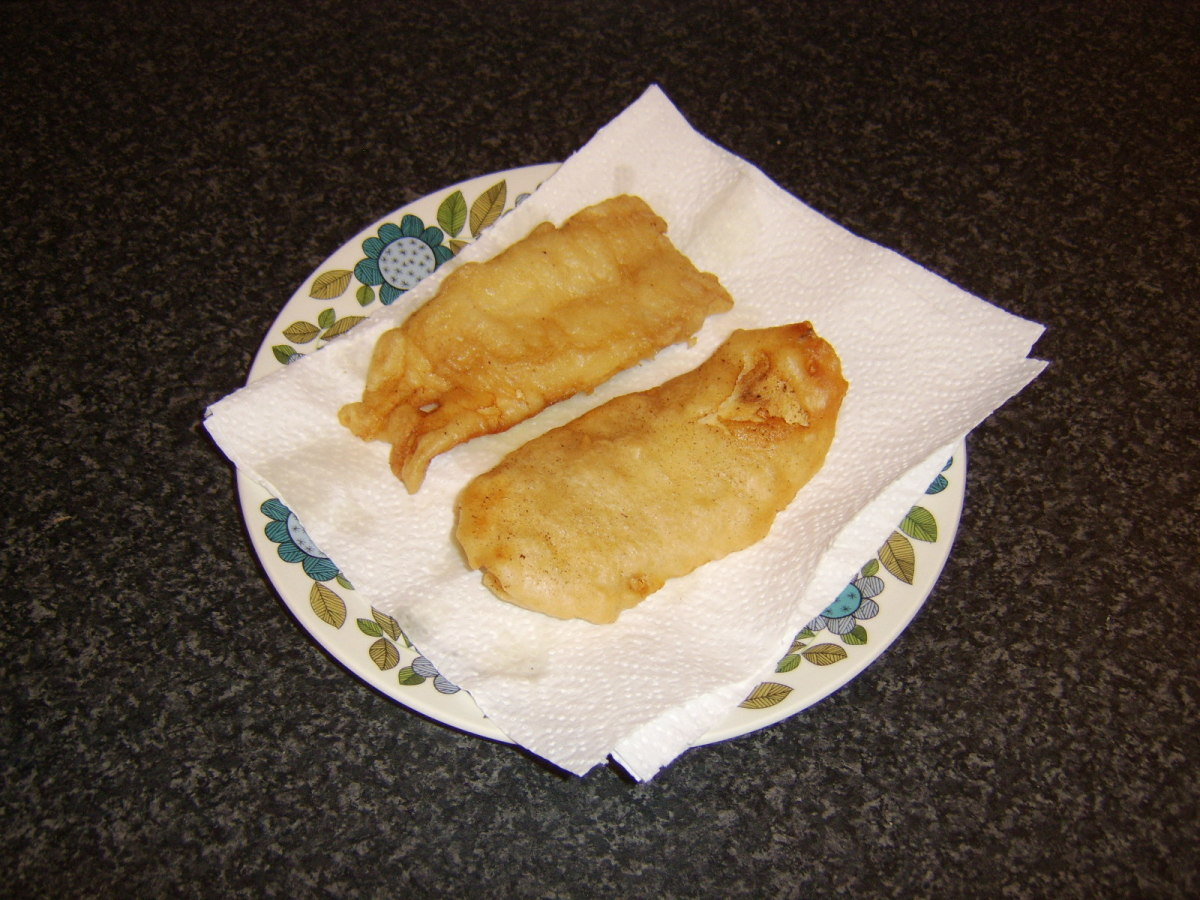 Deep fried whiting is drained on kitchen paper